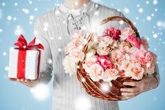 Equipaggi il canestro della tenuta in pieno dei fiori e del contenitore di regalo Fotografia Stock Libera da Diritti