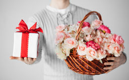 Equipaggi il canestro della tenuta in pieno dei fiori e del contenitore di regalo Fotografia Stock