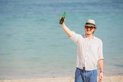 Equipaggi il cappello e gli occhiali da sole d'uso che enjoing la birra in a immagini stock libere da diritti
