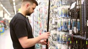 Equipaggi il cliente che sceglie le canne da pesca nel deposito per pescare Lui che prende barretta e che considera la lunghezza archivi video