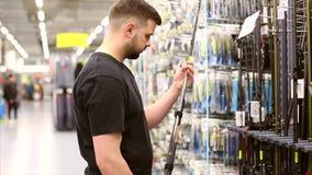 Equipaggi il cliente che sceglie le canne da pesca nel deposito per pescare Lui che prende barretta e che considera la lunghezza video d archivio