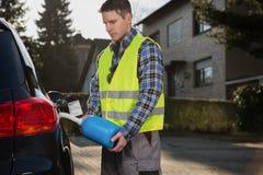 Equipaggi il combustibile di versamento nel carro armato di gas della sua automobile dalla bombola di gas blu Immagine Stock Libera da Diritti