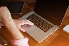 Equipaggi il computer portatile di uso che si siede allo scrittorio di legno con la mano contro la sua bocca Fotografia Stock Libera da Diritti