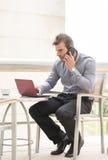 Equipaggi il computer portatile e la conversazione dal telefono nella barra del terrazzo. Fotografia Stock