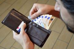 Equipaggi il conteggio dei suoi soldi nell'euro di cuoio del portafoglio Fotografia Stock