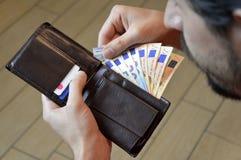 Equipaggi il conteggio dei suoi soldi nell'euro di cuoio del portafoglio Immagini Stock