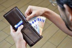 Equipaggi il conteggio dei suoi soldi nell'euro di cuoio del portafoglio Fotografia Stock Libera da Diritti