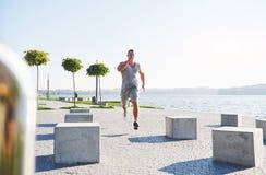 Equipaggi il corridore che fa allungando l'esercizio, preparante per l'allenamento di mattina nel parco Fotografia Stock
