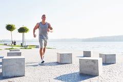 Equipaggi il corridore che fa allungando l'esercizio, preparante per l'allenamento di mattina nel parco Fotografia Stock Libera da Diritti