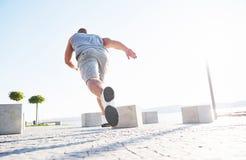 Equipaggi il corridore che fa allungando l'esercizio, preparante per l'allenamento di mattina nel parco Immagine Stock