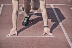 Equipaggi il corridore con le mani muscolari, gambe iniziano sull'eseguire la pista Fotografia Stock