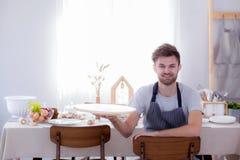 Equipaggi il cuoco unico che sorride guardando la macchina fotografica con il vassoio della tenuta vuoto Immagine Stock