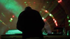Equipaggi il DJ che gioca la musica sulla piattaforma girevole al night-club sul fondo luminoso di illuminazione video d archivio