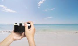 Equipaggi il film della tenuta pronto per la riproduzione fotografica per prendere la foto sopra la spiaggia del mare Fotografia Stock