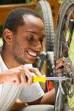 Equipaggi il funzionamento concentrato camicia bianca d'uso sulla riparazione dei meccanici della bicicletta che per mezzo dello  Fotografia Stock Libera da Diritti