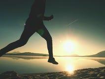 Equipaggi il funzionamento sulla spiaggia contro il contesto di bello tramonto Sabbia del lago della montagna Fotografia Stock