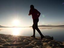 Equipaggi il funzionamento sulla spiaggia contro il contesto di bello tramonto Sabbia del lago della montagna Fotografia Stock Libera da Diritti