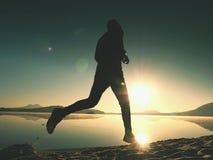 Equipaggi il funzionamento sulla spiaggia contro il contesto di bello tramonto Sabbia del lago della montagna Fotografie Stock Libere da Diritti