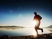 Equipaggi il funzionamento sulla spiaggia contro il contesto di bello tramonto Sabbia del lago della montagna Immagini Stock
