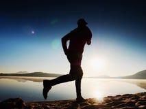 Equipaggi il funzionamento sulla spiaggia contro il contesto di bello tramonto Sabbia del lago della montagna Immagine Stock