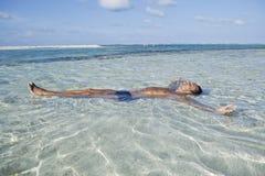 Equipaggi il galleggiamento in acqua sulla spiaggia Immagine Stock
