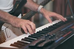 Equipaggi il gioco del piano sulla fase scura drammatica sul fondo vago del giocatore di chitarra immagine stock