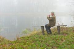 Equipaggi il gioco del sopilka mentre si siedono su un banco sulla riva del fiume Fotografie Stock Libere da Diritti