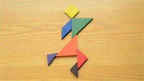 Equipaggi il gioco del tangram di legno che fa le forme differenti dell'essere umano video d archivio