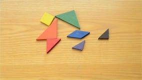 Equipaggi il gioco del tangram di legno e la fabbricazione delle forme differenti dell'essere umano stock footage
