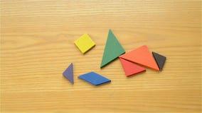 Equipaggi il gioco del tangram di legno e la fabbricazione delle forme differenti dell'essere umano video d archivio