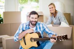 Equipaggi il gioco della chitarra mentre scatole di cartone unpackaging della donna nel fondo Immagine Stock Libera da Diritti