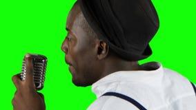 Equipaggi il giovane afroamericano la vista dalla parte posteriore che si avvicina al canto del microfono in uno studio di regist video d archivio
