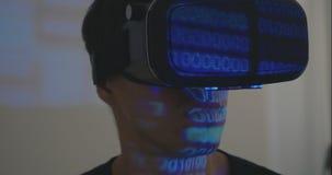 Equipaggi il hemlet d'uso di realtà virtuale del programmatore o i vetri di VR con la riflessione di codice binario stock footage