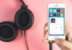 Equipaggi il iPhone della tenuta per giocare la musica dall'applicazione di musica della mela Immagine Stock Libera da Diritti