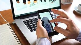 Equipaggi il iphone di uso per comperare ASOS online app sullo schermo video d archivio