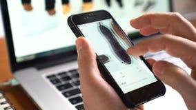 Equipaggi il iphone di uso per comperare ASOS online app sullo schermo stock footage