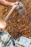 Equipaggi il lavoratore che per mezzo dell'attrezzatura della zappa sulla sporcizia dell'argilla del suolo Immagini Stock Libere da Diritti