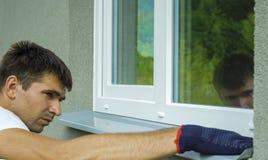 Equipaggi il lavoratore in guanti protettivi che misurano la dimensione esterna del davanzale del metallo della finestra del PVC  fotografie stock libere da diritti