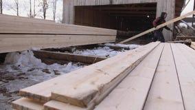 Equipaggi il lavoro ai pacchetti dei bordi di legno imballati immagazzinati nell'iarda della segheria stock footage
