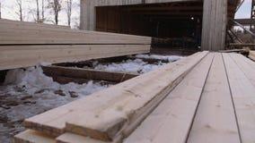 Equipaggi il lavoro alle pile di plance di legno imballate immagazzinate nell'iarda della segheria archivi video