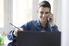 Equipaggi il lavoro con il computer portatile ed il cellulare del computer Fotografia Stock Libera da Diritti