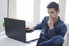 Equipaggi il lavoro con il computer portatile nella stanza Fotografia Stock Libera da Diritti