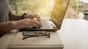 Equipaggi il lavoro con il computer portatile, mani del ` s dell'uomo sul computer portatile Fotografie Stock