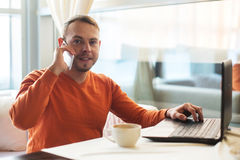 Equipaggi il lavoro con il taccuino, parlante sul telefono, in caffè Fotografia Stock