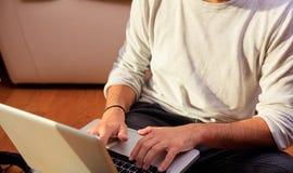 Equipaggi il lavoro con un computer portatile che si siede sul pavimento a casa Fotografie Stock Libere da Diritti