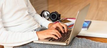 Equipaggi il lavoro con un computer portatile che si siede sul pavimento a casa Fotografia Stock Libera da Diritti