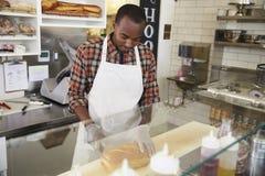 Equipaggi il lavoro dietro il contatore ad una barra del panino fotografie stock libere da diritti