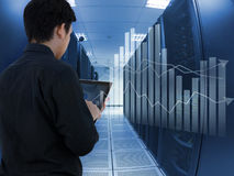 Equipaggi il lavoro nel centro dati ed utilizzi la compressa per analizzano il sistema Immagine Stock Libera da Diritti