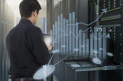 Equipaggi il lavoro nel centro dati ed utilizzi la compressa per analizzano il sistema Fotografia Stock