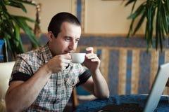 Equipaggi il lavoro in un caffè su un computer portatile Fotografie Stock Libere da Diritti
